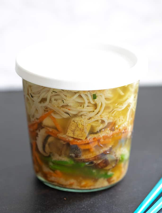Gluten free ramen noodles soup steeping with the cover on.