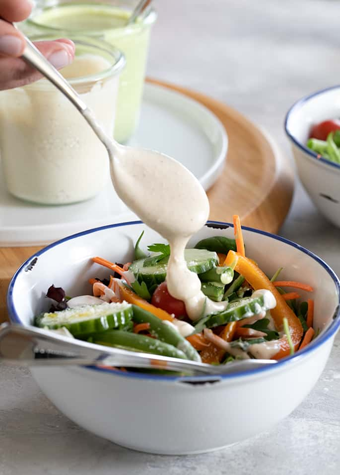 A bowl of food on a table, with Salad and Salad dressing