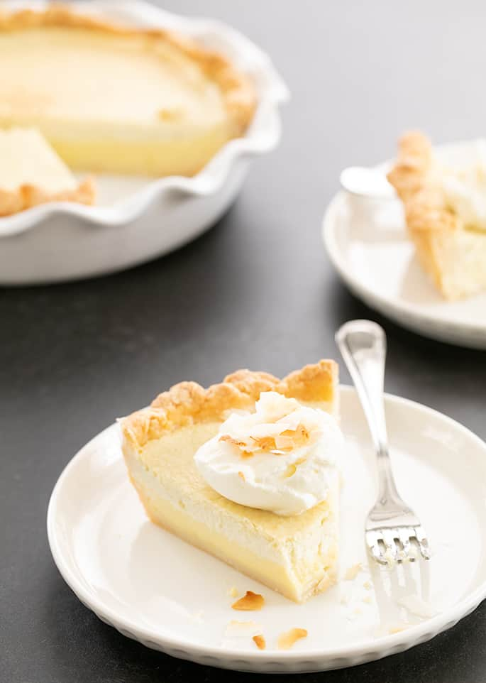 Coconut cream pie slice on a plate and in the pie pan