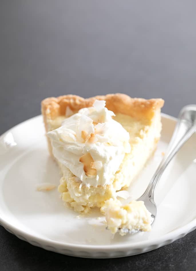 Coconut cream pie slice on plate with forkful