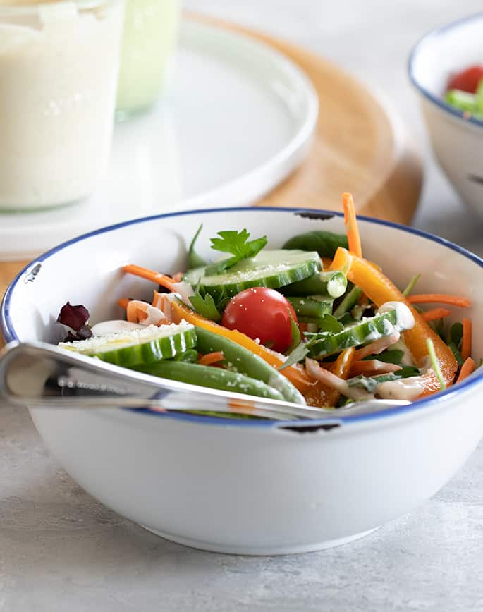 A bowl of salad in a plate with a fork