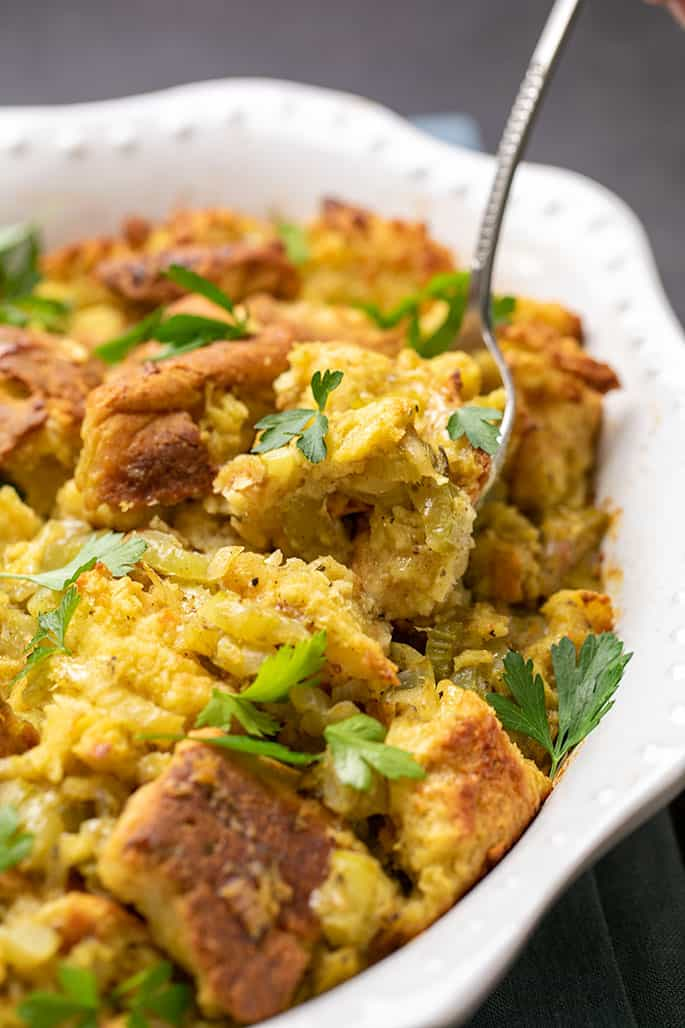Large spoon scooping some baked Thanksgiving stuffing with scattered fresh parsley pieces in white serving dish
