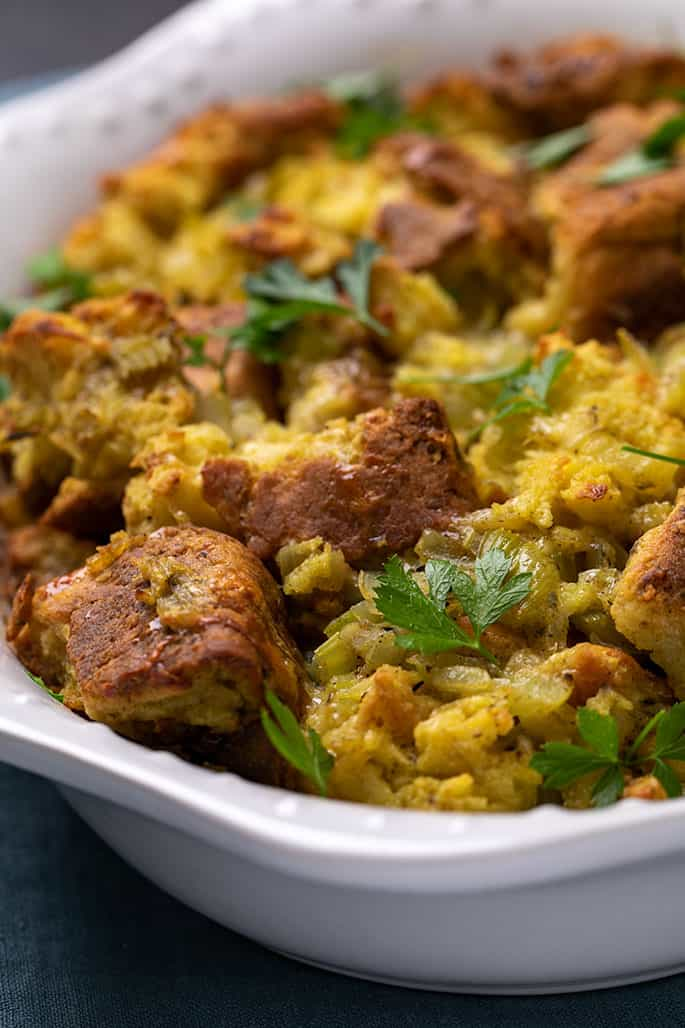 Thanksgiving stuffing with scattered fresh parsley leaves in white casserole dish on blue cloth
