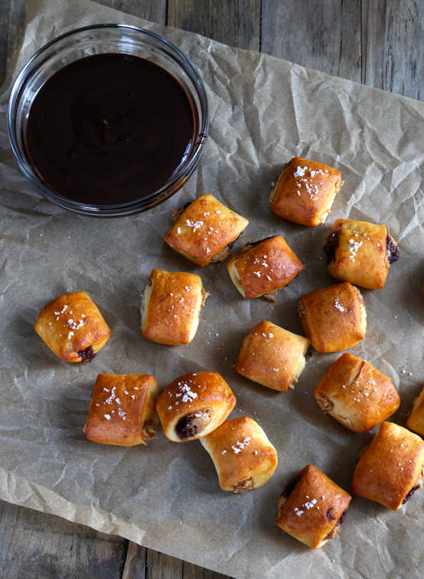 Overhead view of pretzel bites and a bowl of chocolate sauce on brown surface