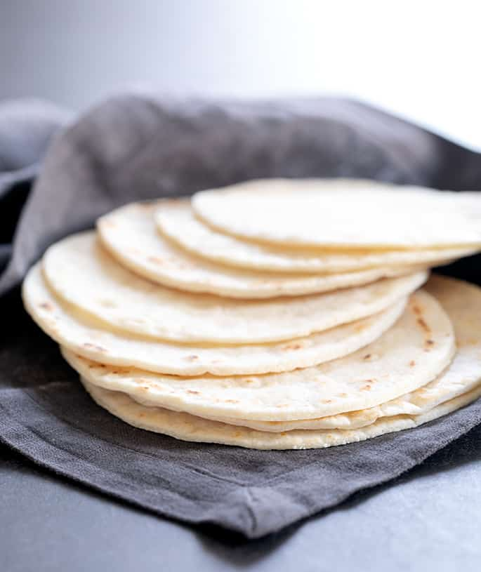 A stack of Paleo tortillas spread out in a cloth