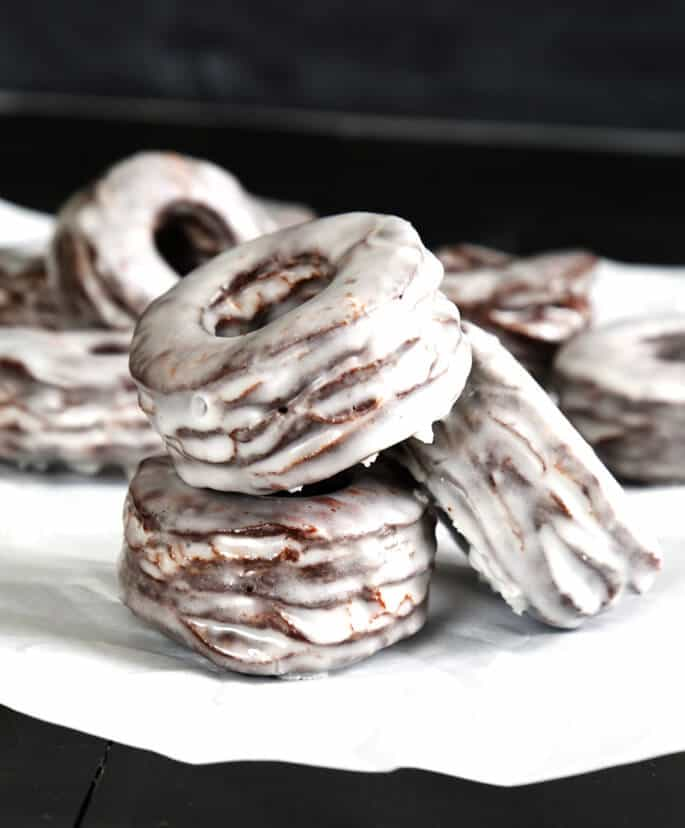 Stack of glazed chocolate donuts on white surface