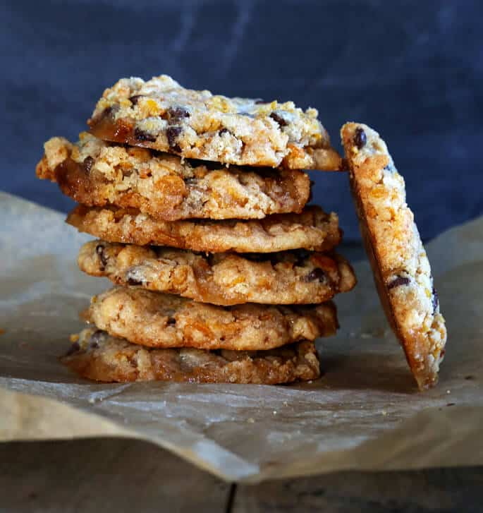 A stack of chocolate chip marshmallow cookies with one leaning on side of stack on brown surface