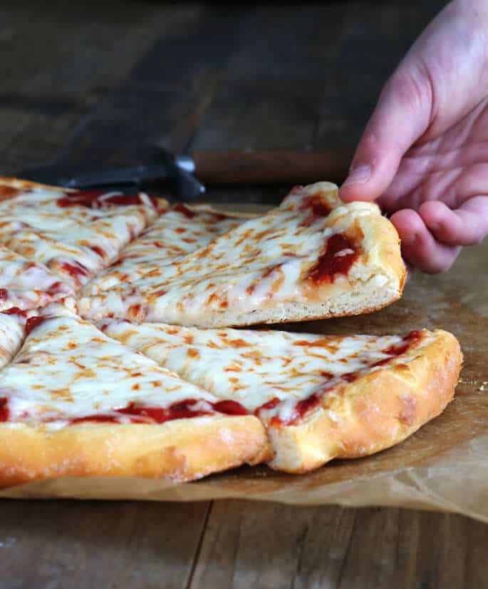 A close up of person taking a slice of pizza from pizza pie