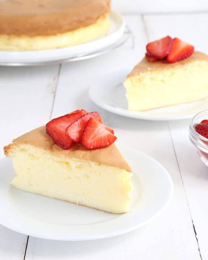 Side view of a slice of Japanese cheesecake on a white plate