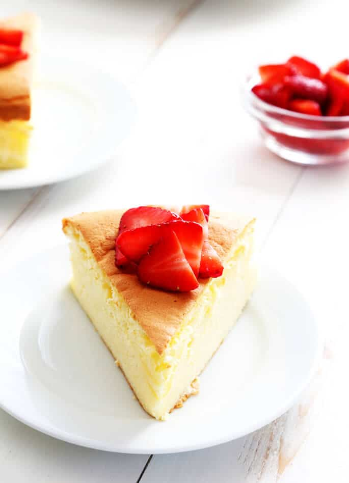 A slice of Japanese cheesecake with strawberries on top on a white plate