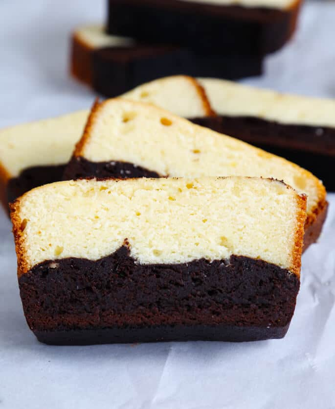 A close up of a slice pf brownie butter cake on white surface