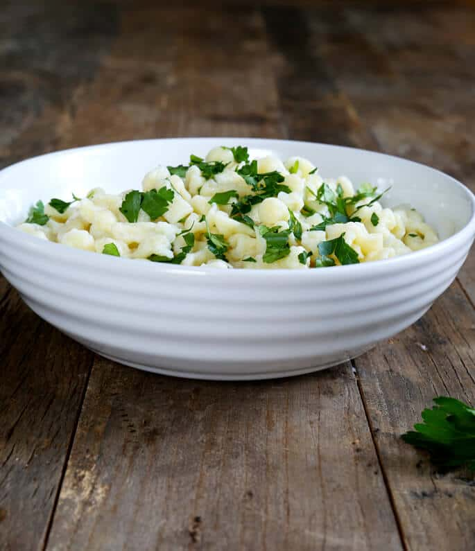 A white bowl with spaetzle and herbs