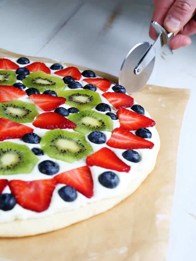 Side view of a fruit pizza being cut