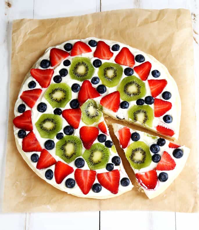 Overhead view off a fruit pizza on beige paper