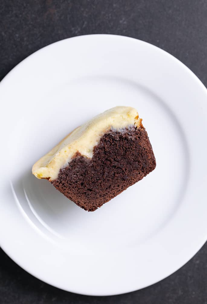 Cheesecake brownie cut in half on small white plate