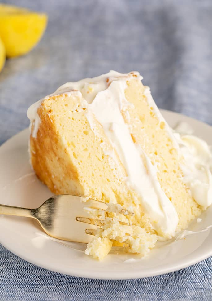 Closeup image of fork with cake crumbs on small white plate with slice of 2 layer lemon cake with lemon in background