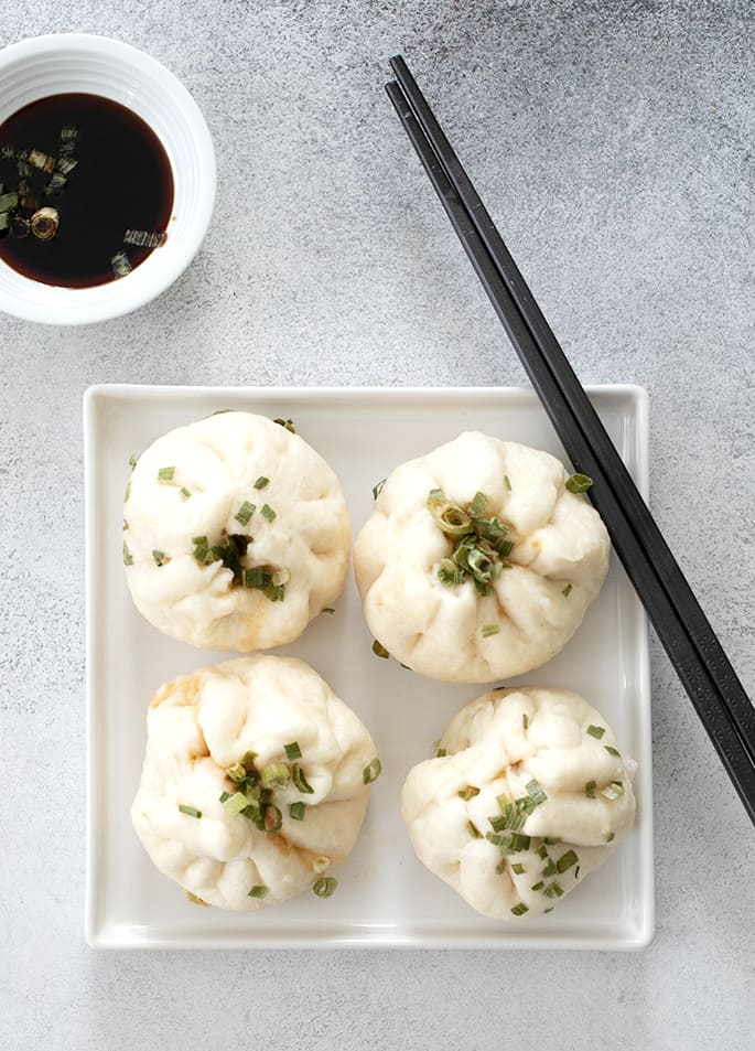 Four Chinese meat buns on a plate with chop sticks and soy sauce in a small bowl