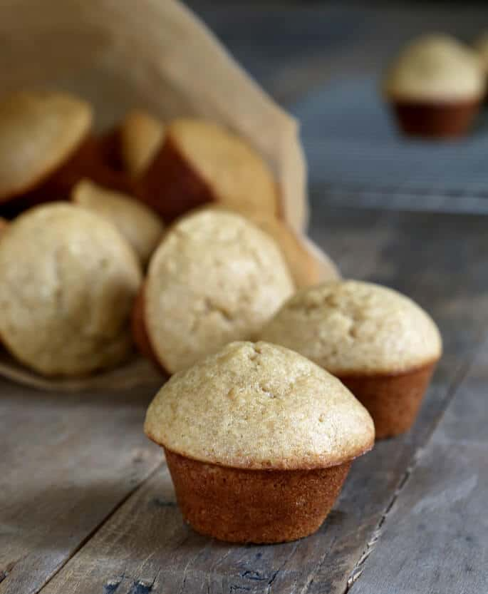 A bag of mini gluten free banana muffins with muffins falling out.
