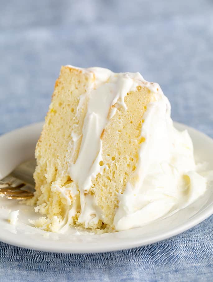 fork on side of slice of 2 layer lemon cake with lots of white frosting on small white plate on blue cloth