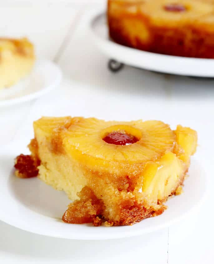 A close up of a piece of pineapple upside down cake on a plate