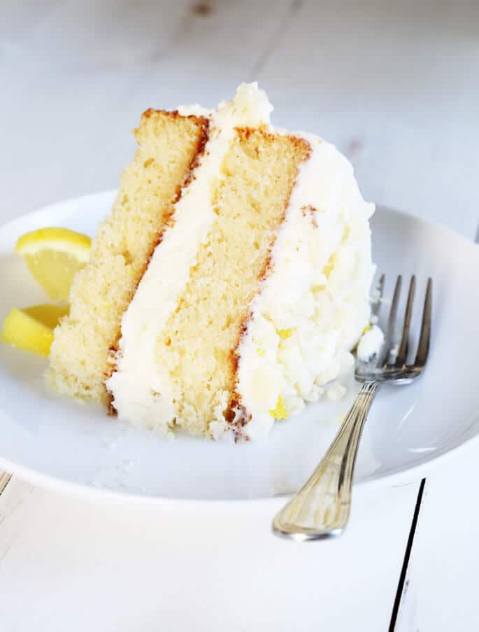 A piece of lemon cream cake on a white plate with a fork and lemon slice