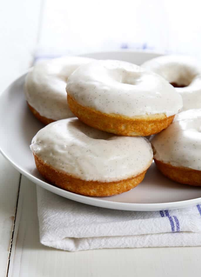 Vanilla cake donuts with white glaze stacked on a platter