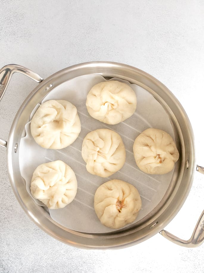 raw shaped Chinese meat buns in a steamer