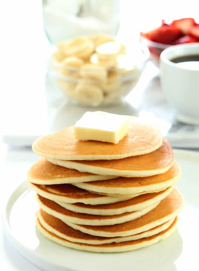 A tall stack of gluten free pancakes with a big pat of butter on top of the stack