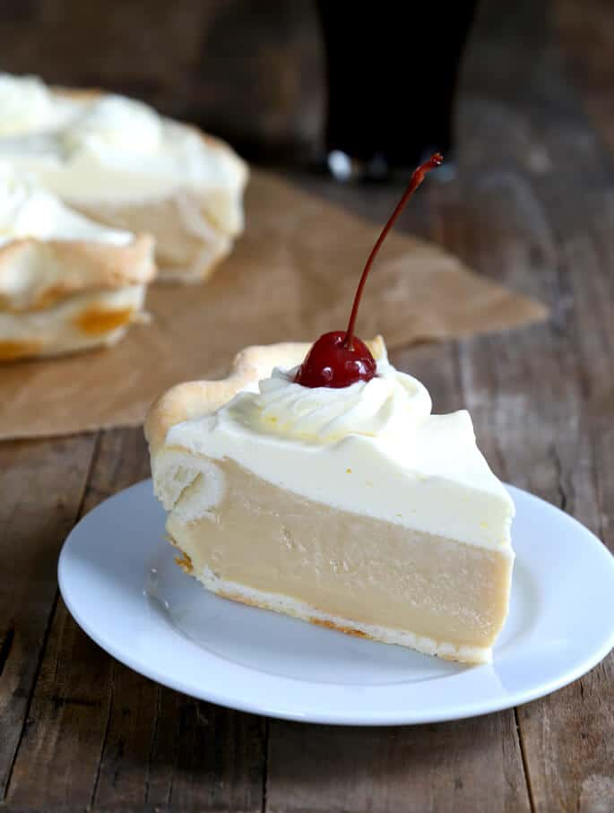 A close up of a slice of root beer pie with cherry on top on white plate