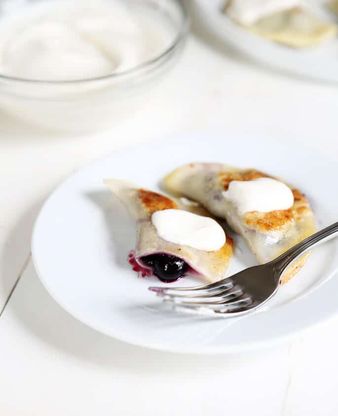 Lightly sweet gluten free pierogi filled with blueberries and topped with sour cream. Perfect!