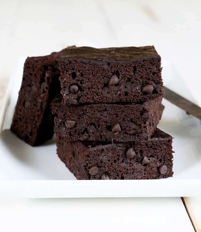 A stack of chocolate zucchini brownies on a white plate