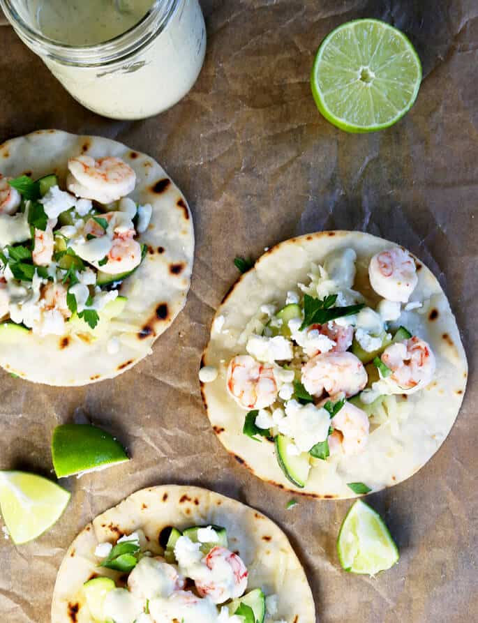 Overhead view of shrimp tostadas on brown surface