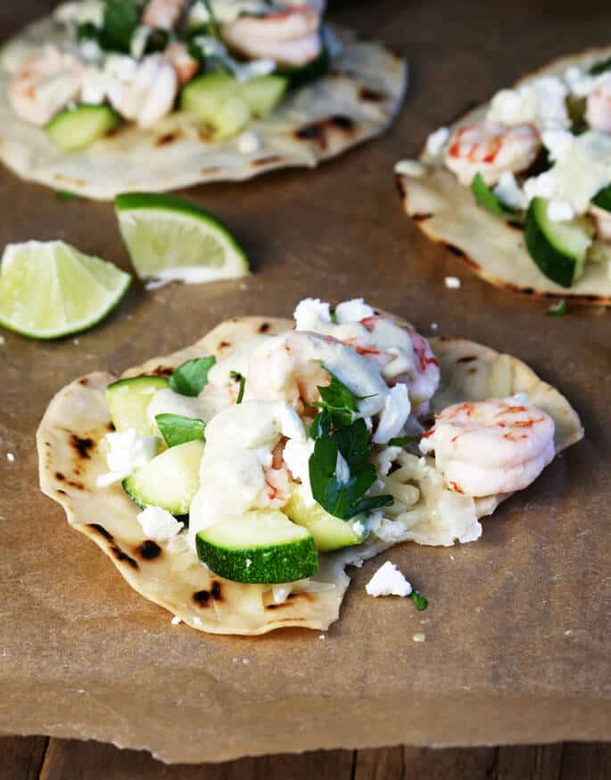 Shrimp tostadas on brown paper with lime slices in back