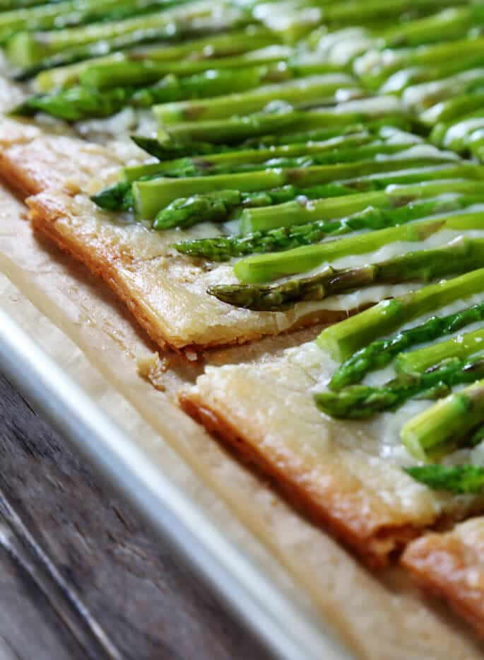 A close up of slices of asparagus tarts on metal tray