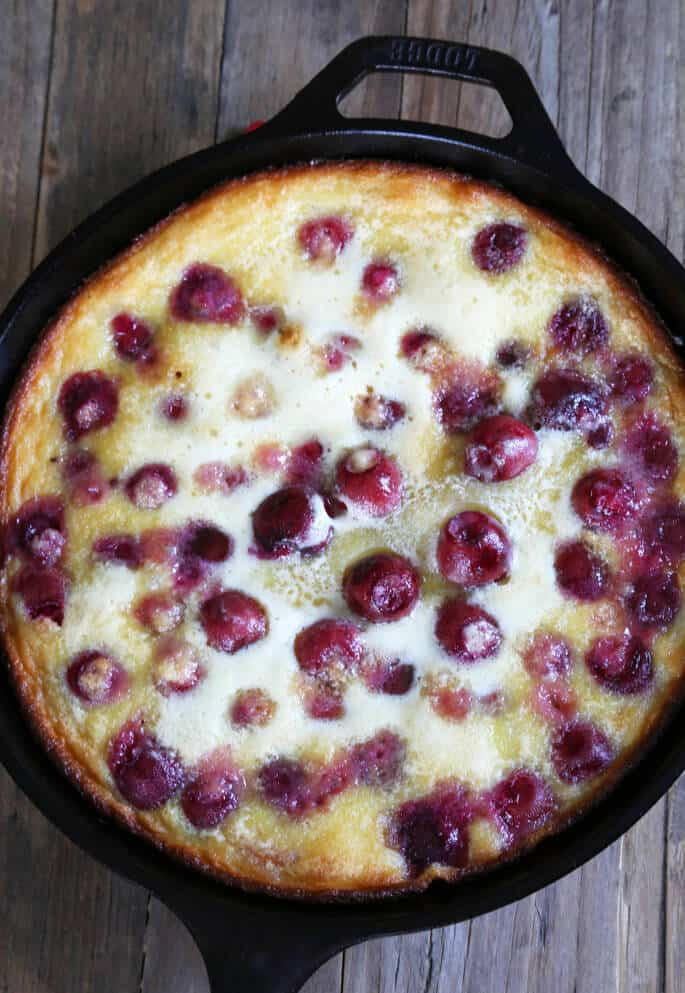 An overhead view of cherry clafoutis on wooden surface