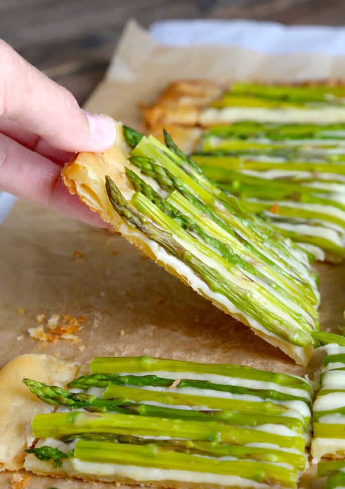Piece of asparagus tart being picked up on parchment paper