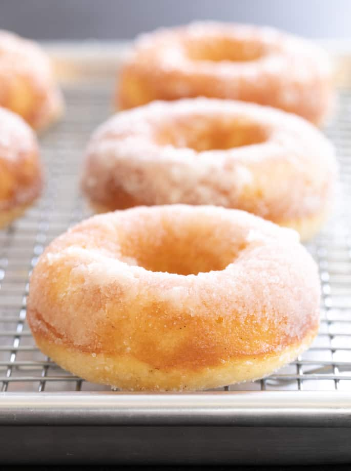 Vanilla cake donuts with a sugar glaze on a wire rack
