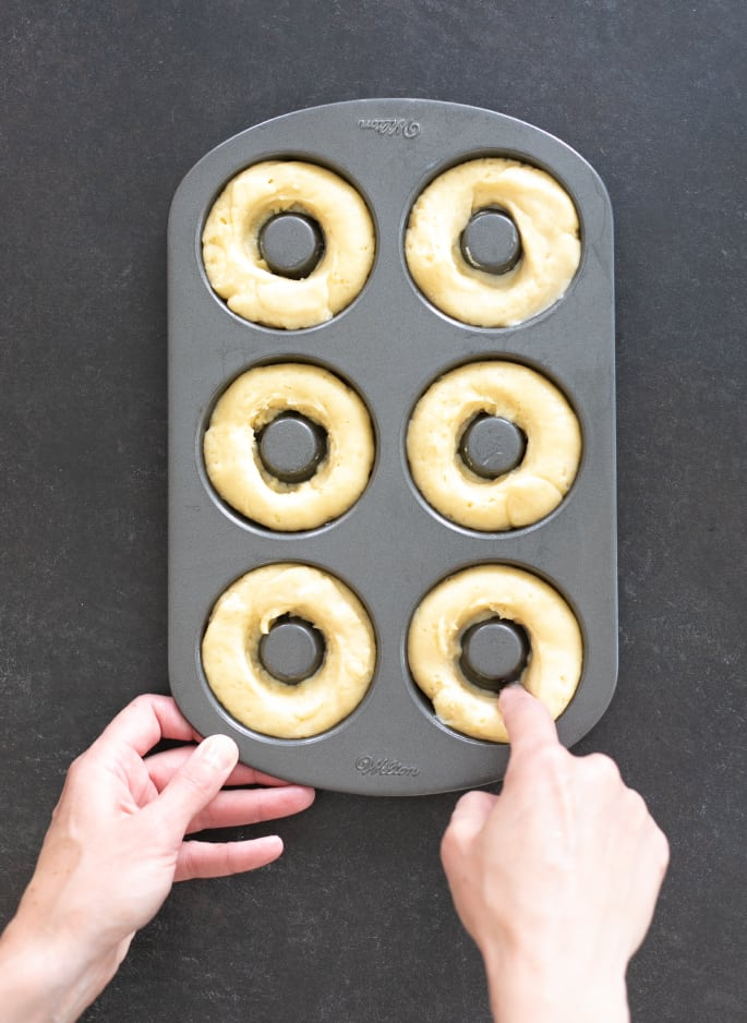 Overhead image of hands shaping vanilla cake donut dough in donut pan