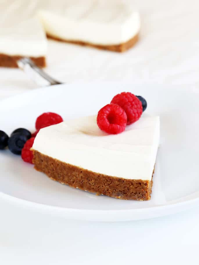 A slice of cheesecake with raspberries and blueberries on top on a white plate