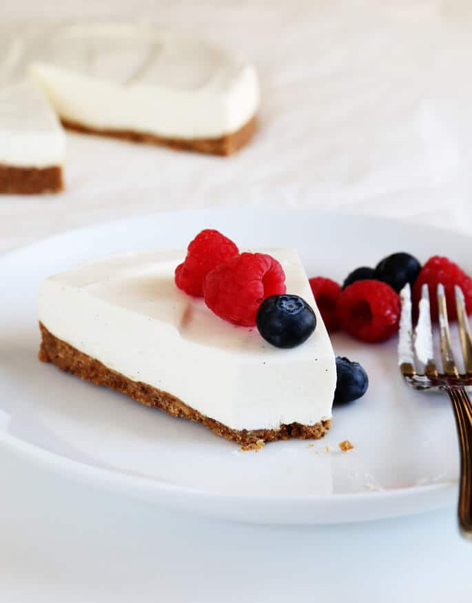 A slice of cheesecake with a bite out of it and raspberries and blueberries on top on a white plate