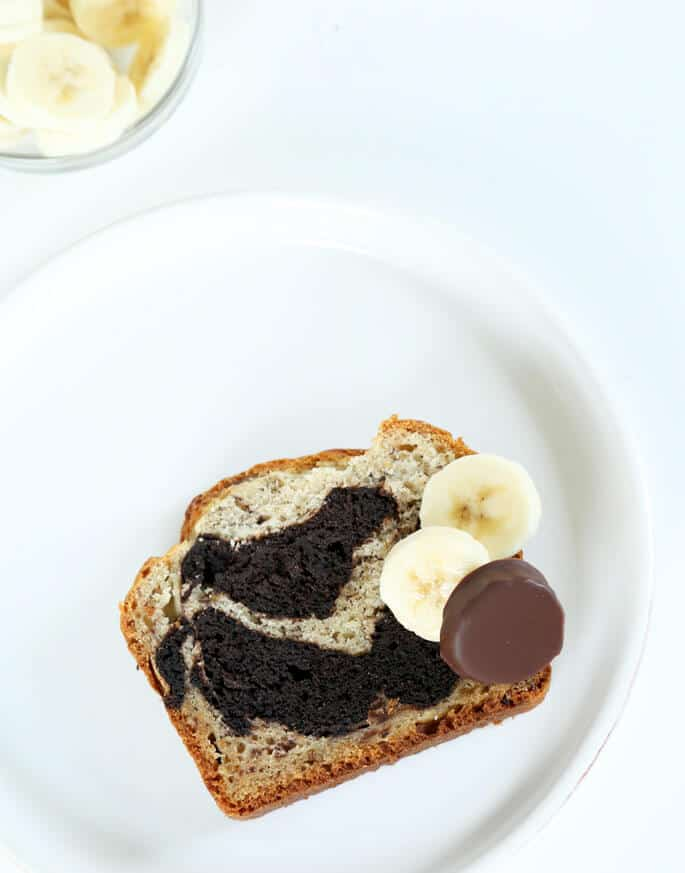 Overhead view of a slice of banana bread with chocolate swirl on a white plate