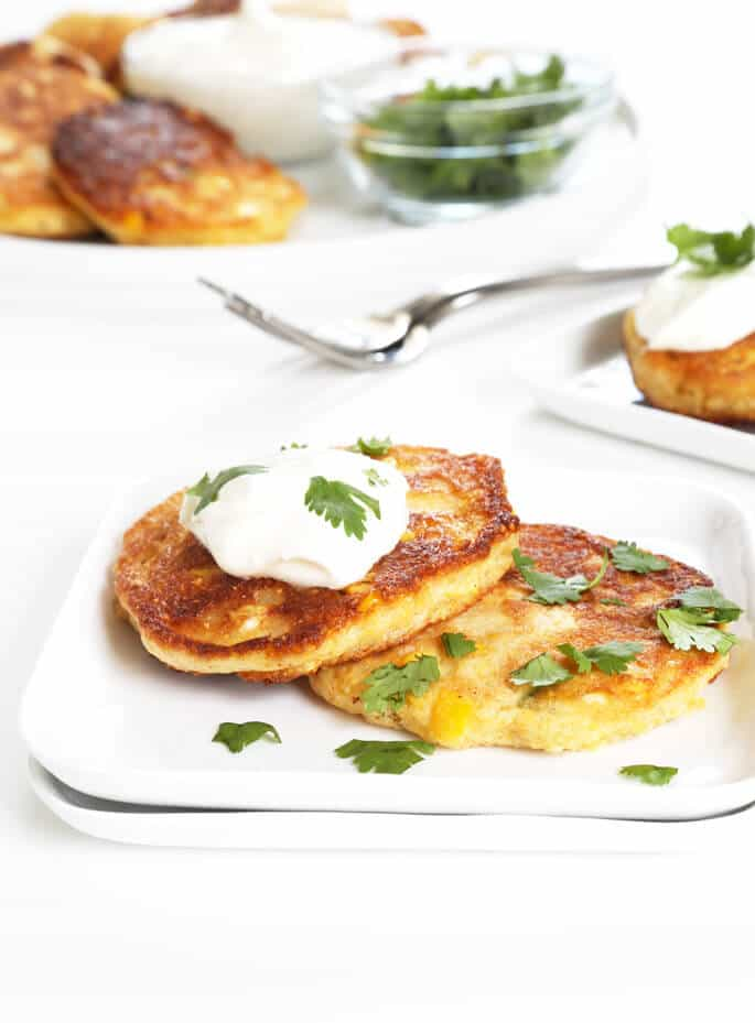 2 corn cakes on a white plate with sour cream and herbs on top