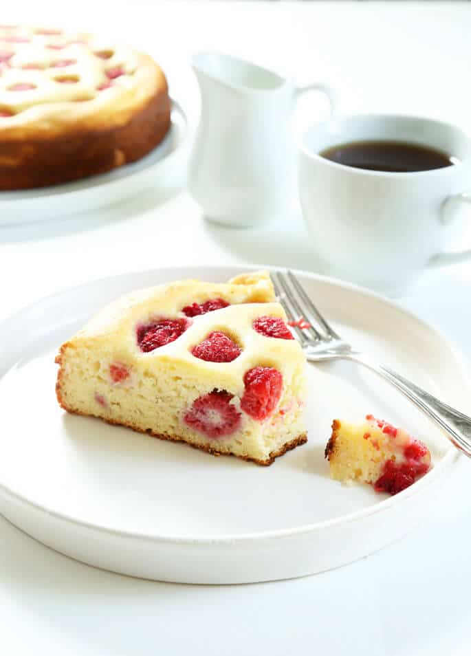 A close up of the inside of a slice of raspberry ricotta cake on a white plate