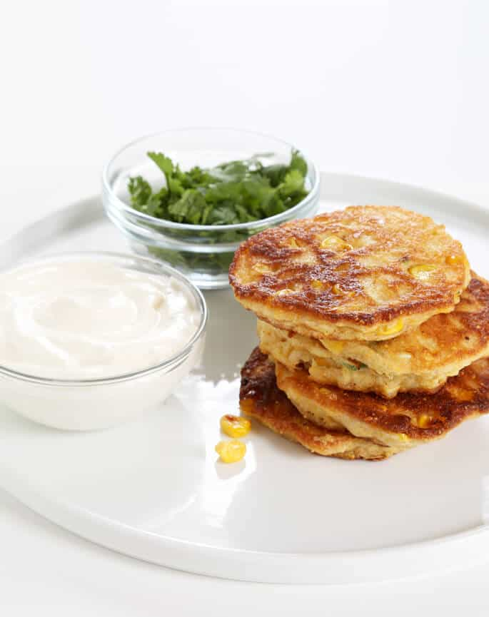 Stack of corn cakes and a bowl of herbs on white plate