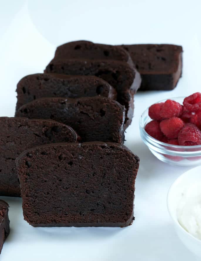 Slices of chocolate pound cake leaning against each other on a white surface with a bowl of raspberries in back