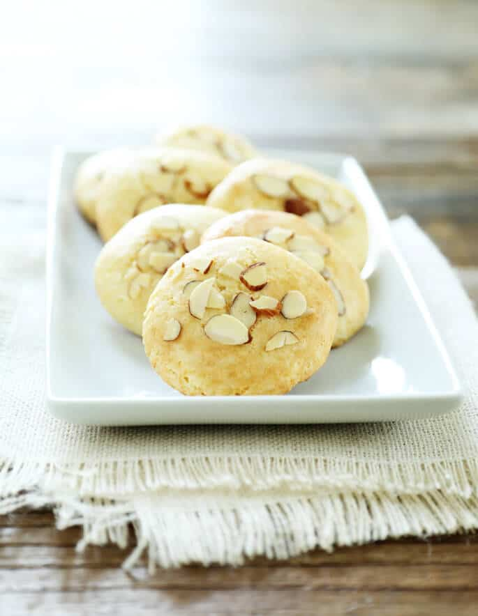 A close up of almond cookies on a white plate