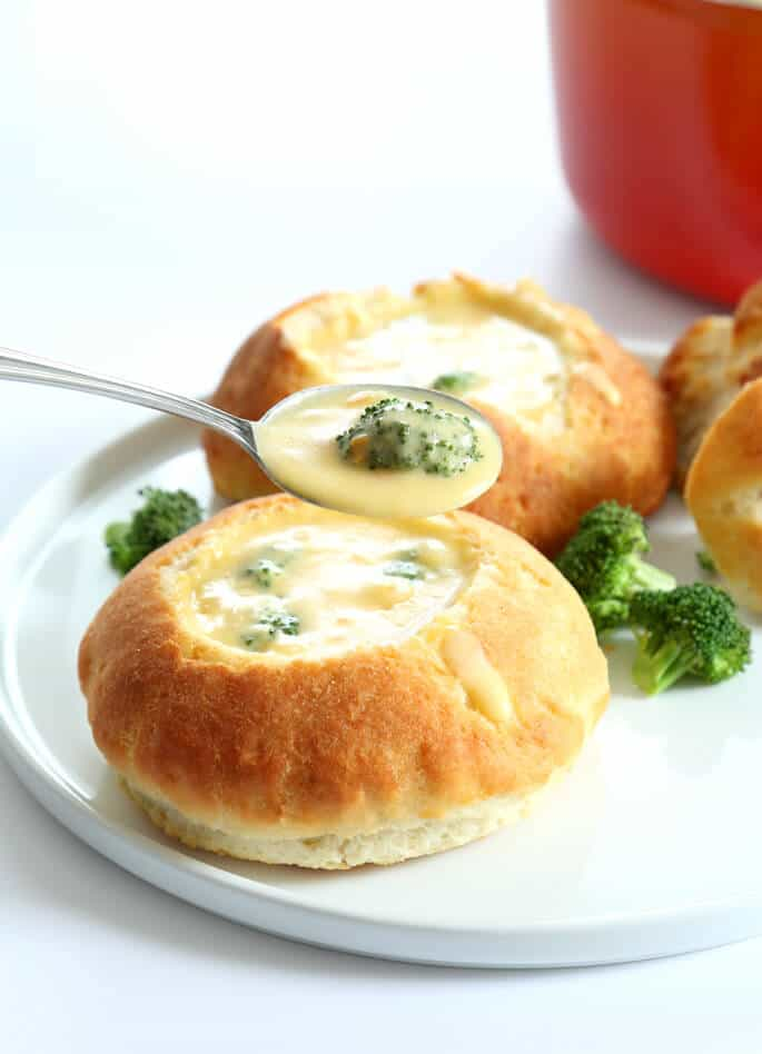 Broccoli cheddar soup in bread bowl with broccoli on white plate and close up of the soup in a spoon