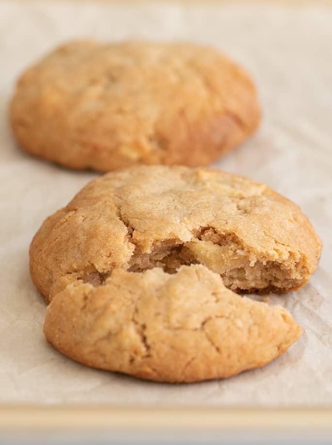 Apple peanut butter cookie broken in half on white paper on tray