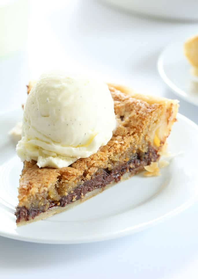 A close up of a slice off chocolate chip pie with a scoop of ice cream on top