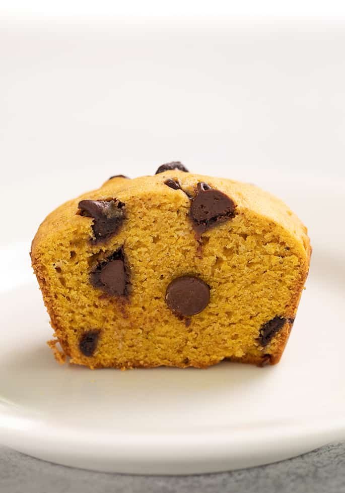 Pumpkin chocolate chip muffin cut in half on small white plate